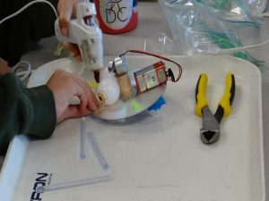 A student gluing the most important feature of a robot, googley eyes!